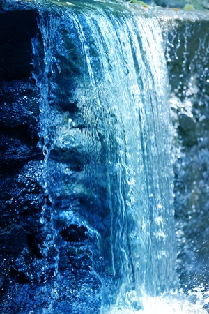 Photo of a close-up of a beautiful mountain waterfall illuminated by the sun