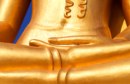 Photo fragment of a beautiful statue of a golden Buddha on an island in Asia sunlit Stock Photo