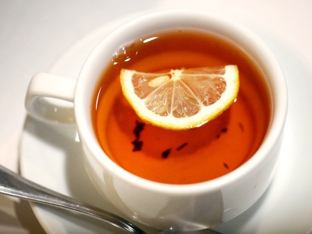 Photo of macro black tea with lemon in a white cup