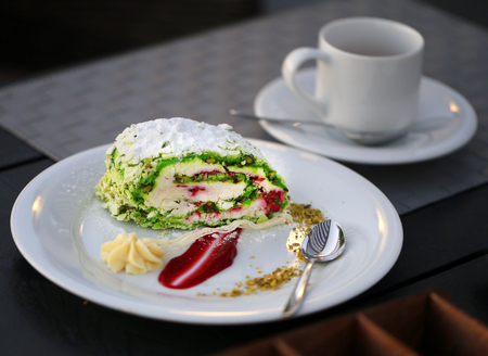 Photo of a bright pistachio cream pie on a plate in a cafe Stock Photo
