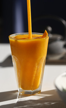 Macro photo of a delicious mango and banana smoothie on a table lit by the sun Stock Photo