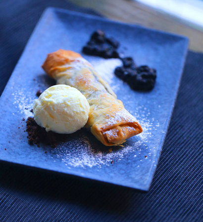 Macro photo of bright blueberry pie and ice cream on a dark plate