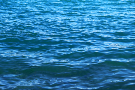 Marine background photo bright blue transparent water with reflections Stock Photo