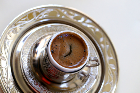 Macro photo of delicious Turkish coffee in a metal cup on a table