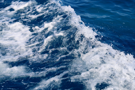 Photo background of blue foaming waves in motion ocean on a sunny day 写真素材