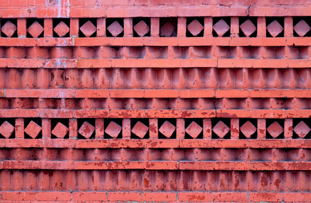 Macro photo of a red ornamental brick wall with different geometric patterns.
