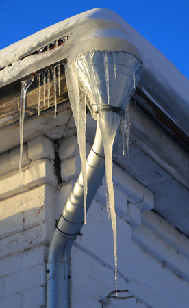 Super fine photo of glittering Icicles on a wooden house roof