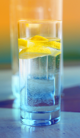 Photo of macro clear water with lemon in a glass glass Cup in a restaurant Stock Photo