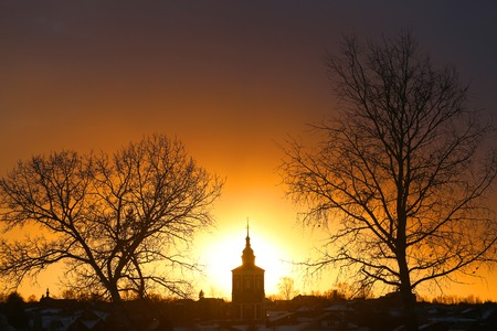 Bright photo of sunset in winter with the temple in the Russian city of Suzdal
