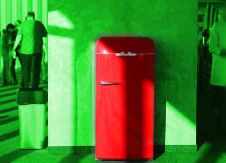 Photo art background unusual red retro fridge on green sunny background