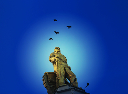 Beautiful photo of the Soviet statue of a man in the city of Moscow against the blue sky