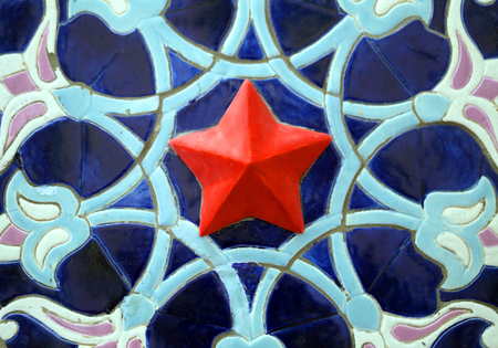 Macro photo of soviet decorative ornament with red star on blue background