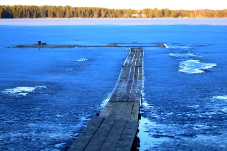 Photo of the pier frozen in the river
