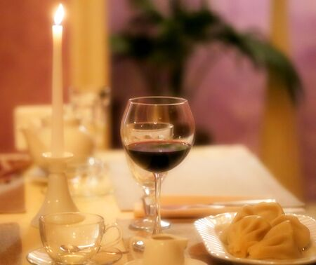 Photo evening romantic table with a glass of wine and dishes with a candle