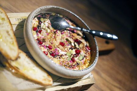Delicious hummus photo with pomegranate seeds in a cafe