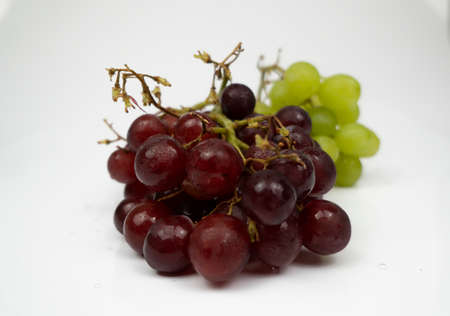 Fresh red and green grapes isolated on white background. Selective focus on the fresh red and green grapes.