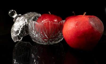 Red apples with water drops, isolated on black background