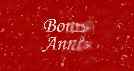 turns of the year: Happy New Year text in French Bonne annee turns to dust from right on red background Stock Photo
