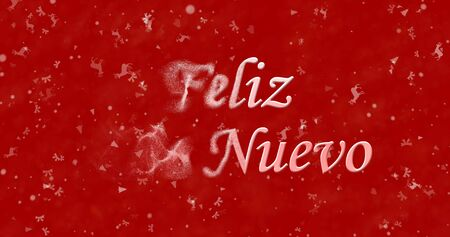 turns of the year: Happy New Year text in Spanish Feliz ano nuevo turns to dust from left on red background Stock Photo