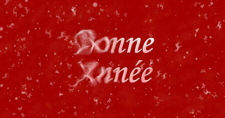 turns of the year: Happy New Year text in French Bonne annee turns to dust from left on red background