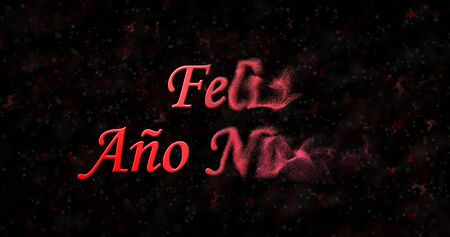 turns of the year: Happy New Year text in Spanish Feliz ano nuevo turns to dust from right on black background