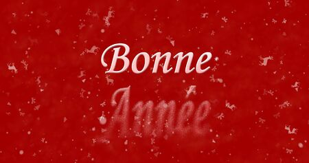 turns of the year: Happy New Year text in French Bonne annee turns to dust from bottom on red background
