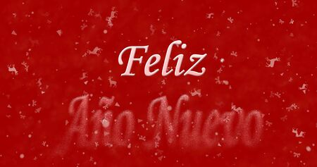 turns of the year: Happy New Year text in Spanish Feliz ano nuevo turns to dust from bottom on red background Stock Photo
