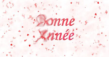 turns of the year: Happy New Year text in French Bonne annee turns to dust from left on white background