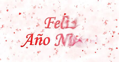 turns of the year: Happy New Year text in Spanish Feliz ano nuevo turns to dust from right on white background