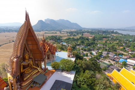 A view from the top of the pagoda, golden buddha statue with rice fields and mountain, Wat Tham Sua, Kanchanburi, Thailand  photo