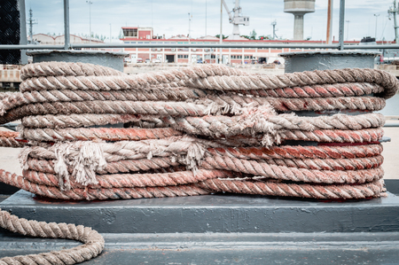 cleat: old rope tied with a ship cleat in port Stock Photo