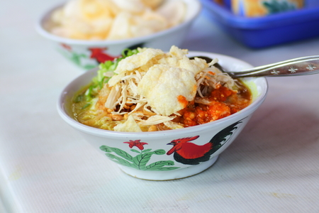 rice porridge, known in Indonesia as bubur ayam, served on the bowl with chicken slices and cracker