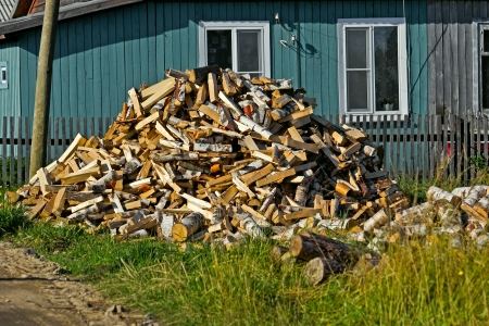 Heap of firewoods in front of a rural house Stock Photo