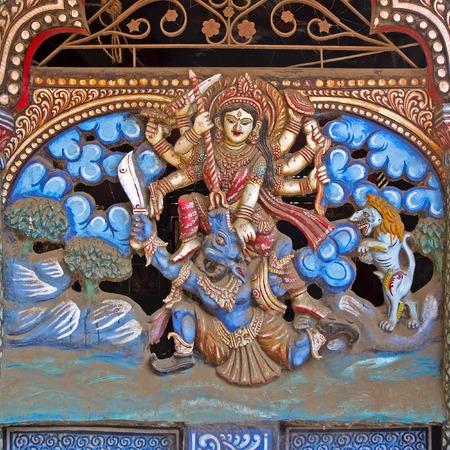 mahishasura: Hindu Goddess Chamunda fighting with demon Mahisha. Sculpture on the wall of ancient Durga temple