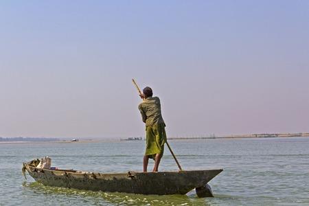 chilika: FEBRUARY 7, 2014, CHILIKA LAKE, ORISSA, INDIA - Unknown fisherman in the boat on Chilika lake
