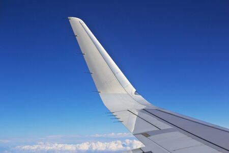 Airplane wing out of window and a blue sky