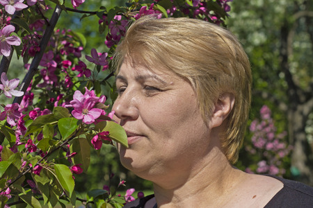 fling: Beautiful mature woman smells an apple flowers in the park