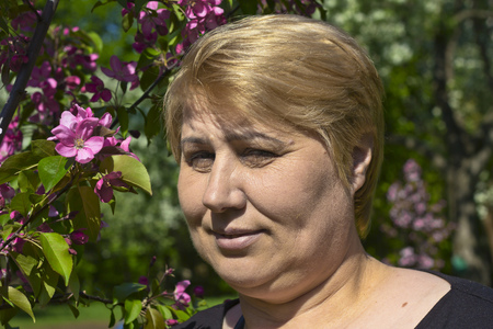 fling: Attractive mature woman close to blossoming apple Stock Photo