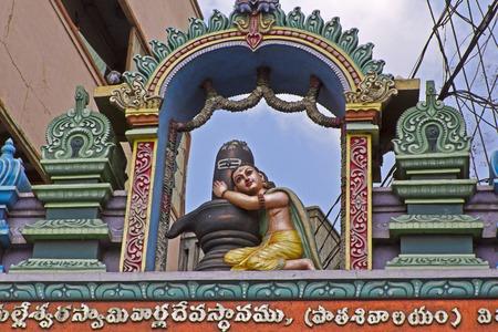 devotions: JANUARY  27, 2015, VIJAYAWADA, ANDHRA PRADESH, INDIA - Bhakta hugs Shiva-Linga, sculpture over the gate of the Hindu temple Stock Photo