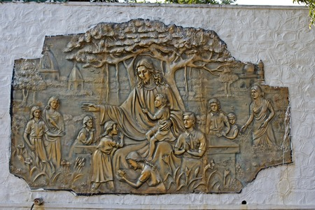 pannel: Metallic pannel with image of Jesus Christ with a children on the wall of christian school Stock Photo