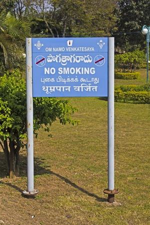 andhra: FEBRUARY 1, 2015, TIRUMALA, ANDHRA PRADESH, INDIA - Billboard with inscription No Smoking in English, Sanskrit, Tamili and Telugu languages on the top of the sacred mountain Tirumala