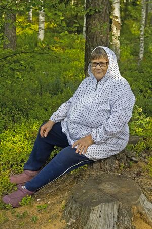 gatherer: Aged woman relaxing on a stump in a forest.  Vladimir area, Russia Stock Photo