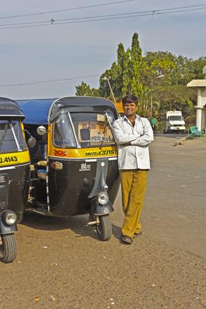 tuktuk: FEB 5, 2015, NASHIK, INDIA - Rickshaw driver close to tuk-tuk