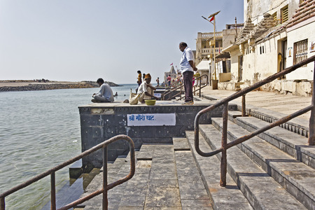 conjunction: FEB 8, 2015, DWARKA, INDIA - Ghat on the point of conjunction of the sacred river Gomati and Arabian sea Editorial