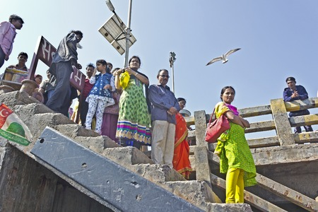 bet: FEB 9, 2015, BET DWARKA, INDIA - Queue of Indian passengers on the pier waits the ferry to drop from Bet Dwarka island TO  OKHA PORT
