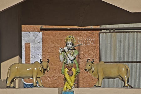 god's cow: FEB 09, 2015,  DWARKA, INDIA - Sculpture of Shri Krishna playing flute andtwo cows over the gate of goshala (farm)