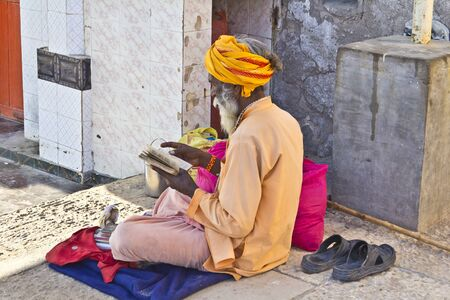 scriptures: FEB 10, 2015, DWARKA, INDIA - Sadhu reads a Holy scriptures on the ghat of river Gomati