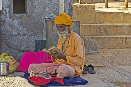 sadhu: FEB 10, 2015, DWARKA, INDIA - Sadhu reads a Holy scriptures on the ghat of river Gomati