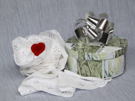 Red heart in laces and a gift in a round box with а bow on a grey background