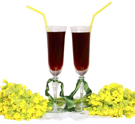 Two glass glasses with wine tubes for a cocktail and bouquets yellow field flowers  photo